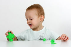 Little boy and modeling clay Stock Photos