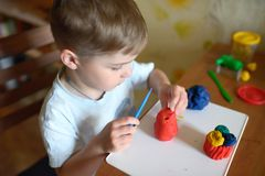 Little boy molds from plasticine Stock Images