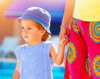 Little boy with mom outdoors. Closeup portrait of cute little boy keep mom's hand and walking outdoors, relaxation near poolside, summer vacation, loving family Stock Photo