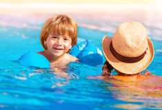 Little boy with mom in the pool. Closeup on cute little boy with mother swimming in the pool, happy family having fun in water, summer vacation, fun and royalty free stock image