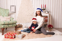 Little boy with mom posing in Christmas interior Royalty Free Stock Photo