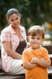 Little boy with mom standing arms crossed. Little happy casual caucasian boy with mom standing arms crossed. Parent in background, smiling. Looking at camera Royalty Free Stock Photography