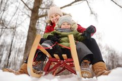 Little boy and mother enjoy sliding on the snow slide royalty free stock images