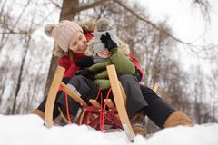Little boy and mother enjoy sliding on the snow slide stock photos