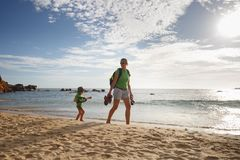 Little boy with mother on a family hike by the tropical sea. Travelling with children, beach hopping, family time, active lifestyle, beach fun concept royalty free stock image