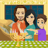 Little boy with mother and father lighting Hanukkah menorah Royalty Free Stock Images