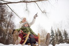Little boy and mother/grandmother/nanny sliding in the Park stock image