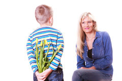 Little boy with mother hold flowers behind back. Stock Photo