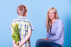 Little boy with mother hold flowers behind back. Royalty Free Stock Image