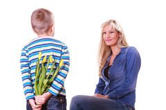 Little boy with mother hold flowers behind back. Royalty Free Stock Photo
