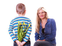 Little boy with mother hold flowers behind back. Royalty Free Stock Photos