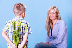 Little boy with mother hold flowers behind back. Stock Image