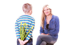 Little boy with mother hold flowers behind back. Royalty Free Stock Photography