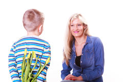 Little boy with mother hold flowers behind back. Stock Photography