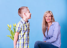 Little boy with mother hold flowers behind back. Royalty Free Stock Images