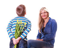 Little boy with mother hold flowers behind back. Stock Images
