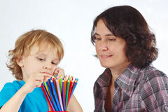 Little boy with mother looks on color pencils Stock Photography