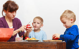 Little boy and mother peeling apples with knife Stock Image