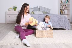 Little boy, mother play with toys in basket in bedroom Royalty Free Stock Photography