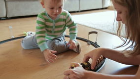 Little boy with mother playing with toy train. HD stock footage