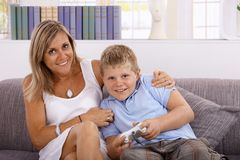 Little boy and mother playing video game smiling Stock Image