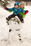 Little boy and mother posing on big snowman Royalty Free Stock Photo