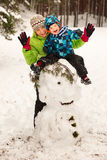 Little boy and mother posing on big snowman Royalty Free Stock Photos