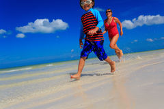 Little boy and mother running on beach Stock Photos