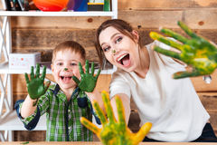 Little boy and mother showing hands painted in colorful paints Stock Photography