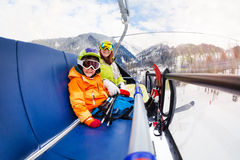 Little boy and mother on ski lift chair. Young women with little boy sitting on chair on ski lift wearing ski mask and helmet smiling to camera Stock Image