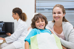 Little boy and mother smiling at camera with dentist in background Stock Photos