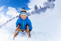 Little boy in mountains slide on sledge Stock Photos