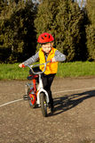 Little boy mounting his bicycle Stock Photos