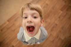 Little boy with a mouth open in screaming. View from above Stock Image