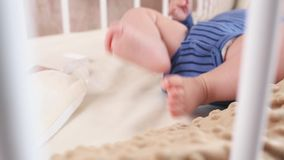 Little boy moving his legs. Cute happy 6 month baby boy lying and playing stock footage