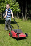 Little boy mowing lawn Stock Photos