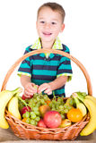 Little boy munching on fruit basket Stock Photo