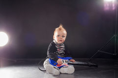 Little boy musician playing rock music on the guitar Stock Images