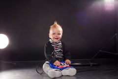 Little boy musician playing rock music on the guitar Stock Photos