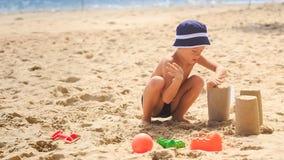 Little Boy na cubeta das suficiências das ocupas do chapéu com a areia na praia filme