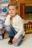 Little boy near the Christmas tree and fireplace in the new year stock image
