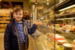 Little boy near display with cakes Royalty Free Stock Image