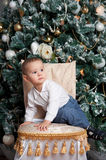 Little boy near fir tree with Christmas gift. Indoor Stock Photo