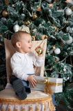 Little boy near fir tree with Christmas gift. Indoor Royalty Free Stock Photos