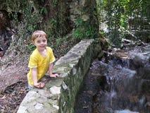 Little boy near a mountain river spring. Toddler having fun near a river ''Vrelo'' in Perucac, Serbia royalty free stock photography