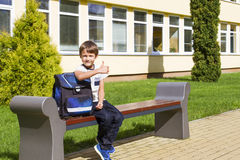 Little boy near preschool sitting on the bench. Child smiling. He feeling very excited about going back to school. Outdoor Royalty Free Stock Images