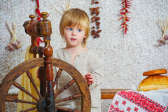 Little boy near spinning wheel Stock Images