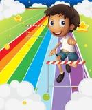 A little boy near the stripe hurdle Royalty Free Stock Photography