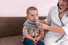 Little boy with nebulizer mask on his face stock photography