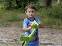 Little Boy nel parco Giocando con un aeroplano del ` s dei bambini fotografia stock libera da diritti
